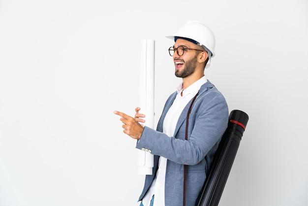 Hombre joven arquitecto con casco y sosteniendo planos aislados en la pared blanca apuntando con el dedo hacia un lado y presentando un producto