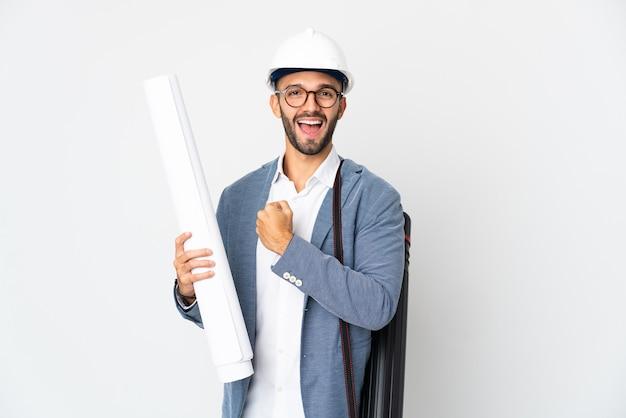 Hombre joven arquitecto con casco y sosteniendo planos aislados en la pared blanca celebrando una victoria