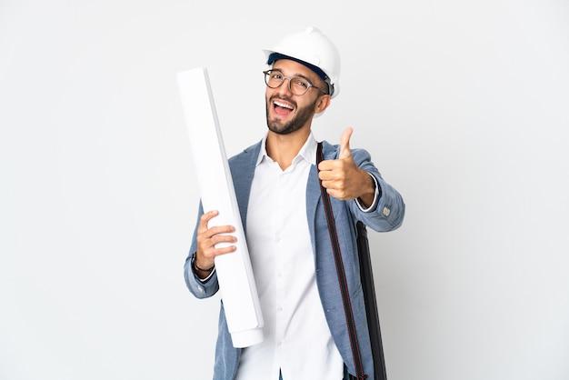 Hombre joven arquitecto con casco y sosteniendo planos aislados en la pared blanca con los pulgares hacia arriba porque algo bueno ha sucedido