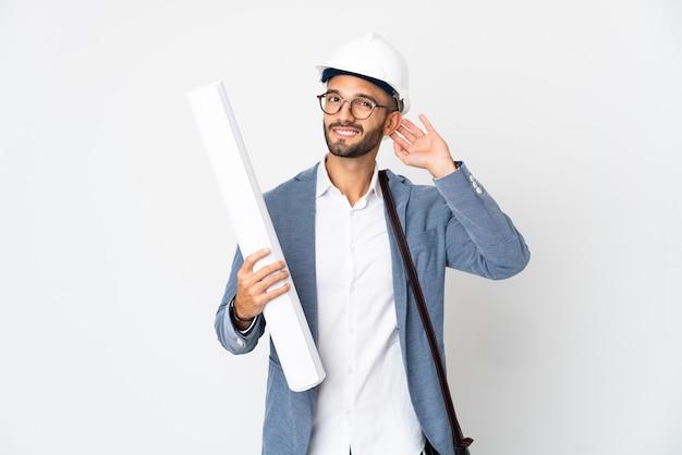 Hombre joven arquitecto con casco y sosteniendo planos aislados en la pared blanca que tiene dudas