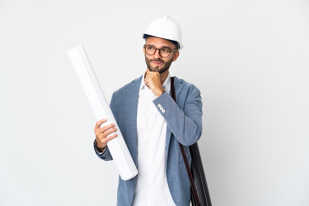 Hombre joven arquitecto con casco y sosteniendo planos aislados en la pared blanca teniendo dudas y pensando