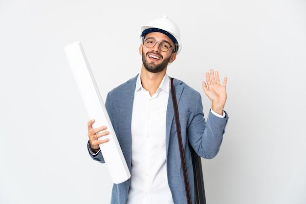 Hombre joven arquitecto con casco y sosteniendo planos aislados sobre fondo blanco saludando con la mano con expresión feliz