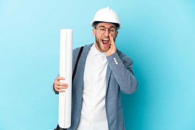 Hombre joven arquitecto con casco y sosteniendo planos sobre pared aislada gritando con la boca abierta