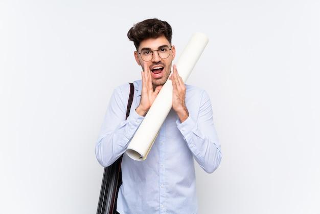 Hombre joven arquitecto sobre gritos blancos aislados con la boca abierta