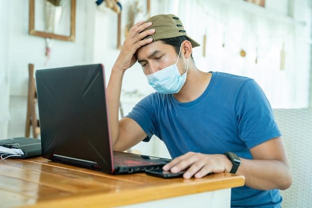 Hombre joven asiático independiente con mascarilla que trabaja con la computadora portátil y se siente triste