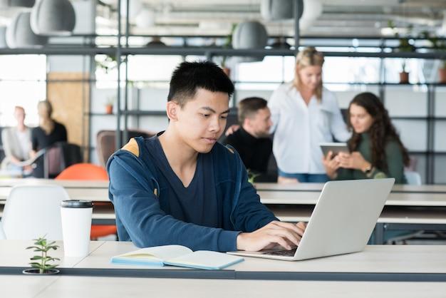 Hombre joven asiático que trabaja con la computadora portátil