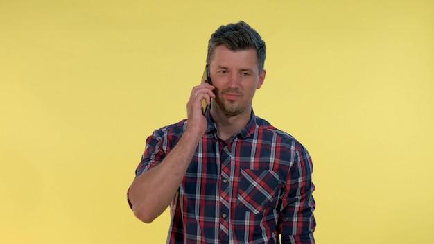 Hombre joven de aspecto agradable hablando con alguien por teléfono inteligente sobre fondo amarillo.