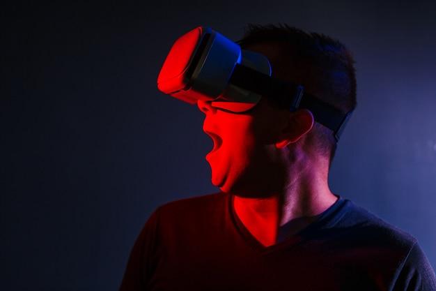 Hombre joven asustado en los vidrios del vr 3d en fondo oscuro con la iluminación azul roja