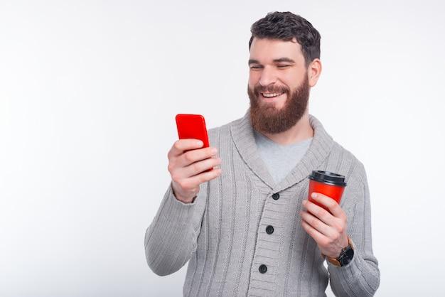 El hombre joven está atando un mensaje en su teléfono y está sosteniendo una taza roja para ir en el fondo blanco.