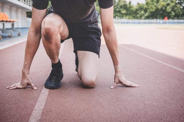 Hombre joven atleta de fitness preparándose para correr en pista, concepto de bienestar ejercicio entrenamiento