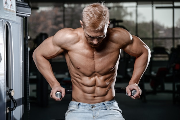 Hombre joven atlético fuerte y guapo músculos abdominales y bíceps