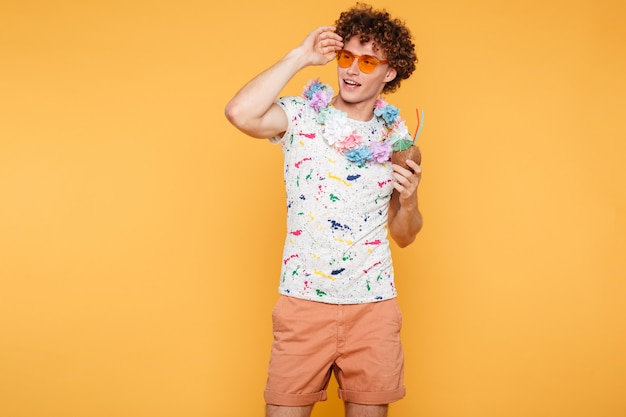 Hombre joven atractivo en gafas de sol con cóctel de coco