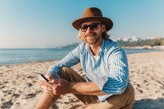 Hombre joven atractivo hipster sentado en la playa por el mar en vacaciones de verano