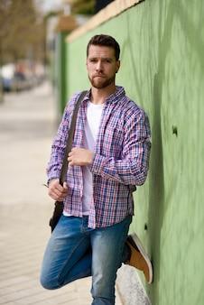 Hombre joven atractivo que se coloca en fondo urbano. concepto de estilo de vida