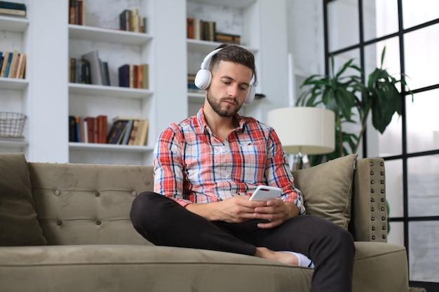 Hombre joven atractivo que se relaja en un sofá en casa y que usa el teléfono móvil para cheking redes sociales.