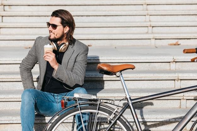 Un hombre joven atractivo que sostiene la taza de café para llevar que se sienta en las escaleras cerca de la bicicleta