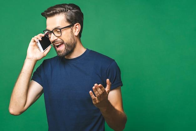 Hombre joven atractivo con smartphone en fondo de color