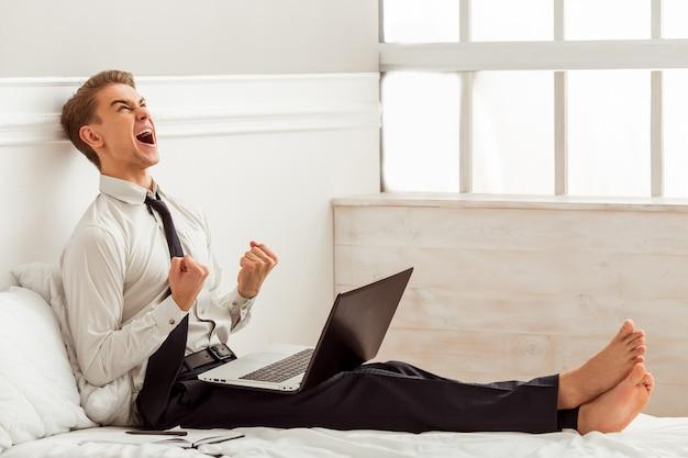 El hombre joven atractivo está utilizando la computadora portátil mientras que se sienta en cama.
