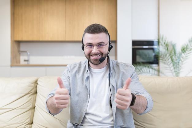 Hombre joven con auriculares mirando al frente y usando video chat en la oficina en casa