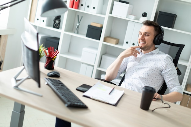 Un hombre joven en auriculares se sienta en un escritorio de la computadora