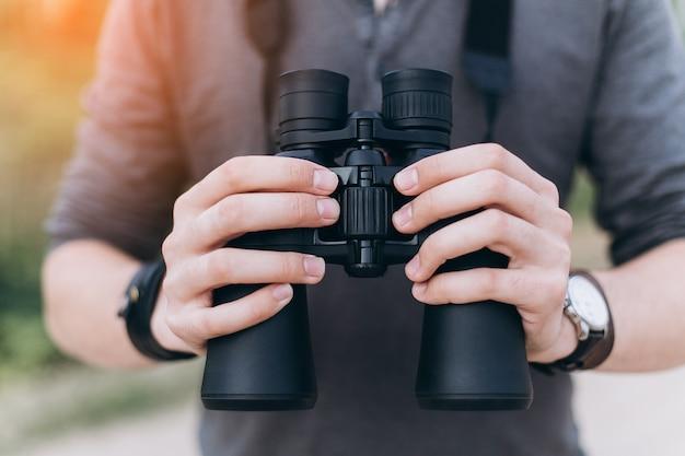 Hombre joven aventura viajando con binoculares en manos