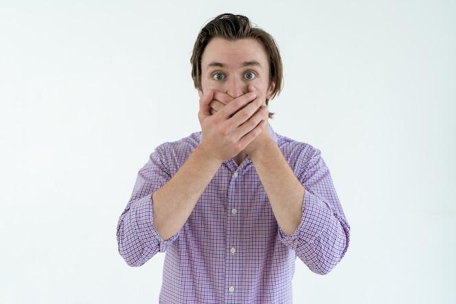 Hombre joven avergonzado que cubre la boca con ambas manos. concepto de  vergüenza 9caa2582770