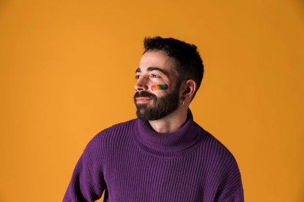 Hombre joven con bandera de arcoiris lgbt en la cara