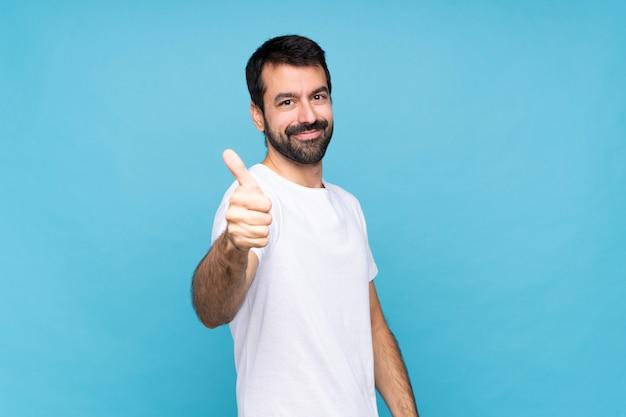 Hombre joven con barba aislado con pulgares arriba porque algo bueno ha sucedido