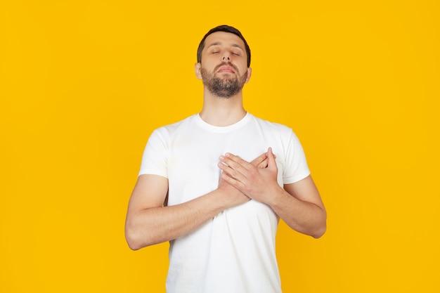 Hombre joven con barba con camiseta blanca sonriendo, poniendo sus manos sobre su pecho con los ojos cerrados y un gesto de agradecimiento en su rostro.