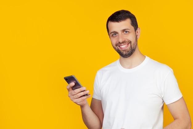 Hombre joven con barba en una camiseta blanca está usando un teléfono inteligente con una cara feliz de pie y sonriendo con una sonrisa segura mostrando los dientes.