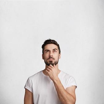 Hombre joven con barba y camiseta blanca