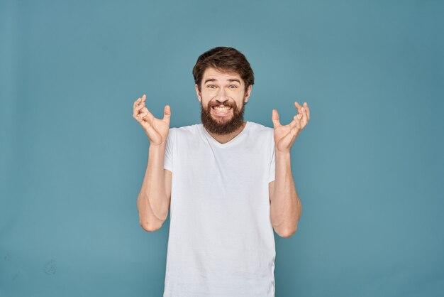 Un hombre joven con barba en una camiseta muestra diferentes emociones, diversión, tristeza, ira en el espacio.