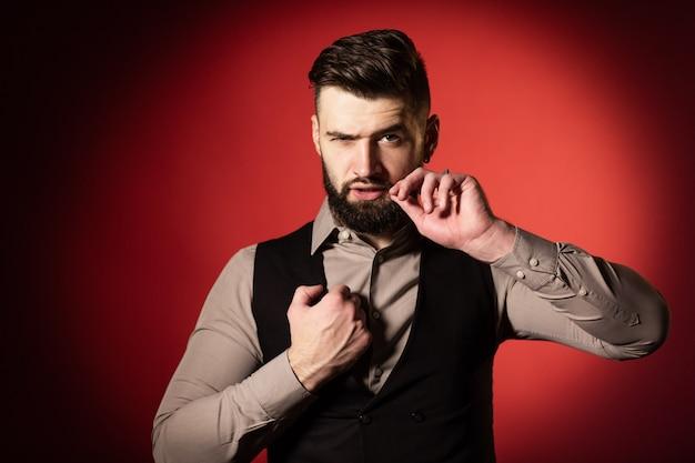 Hombre joven con barba en chaleco negro posando en estudio con fondo rojo. un hombre se endereza el bigote con la mano. de cerca
