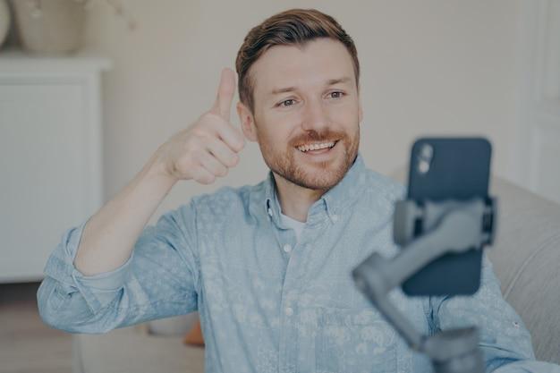 Hombre joven con barba corta que muestra el pulgar hacia arriba gesto mientras chatea por video en el teléfono conectado al cardán en el interior, habla con sus familiares y les dice que todo está bien