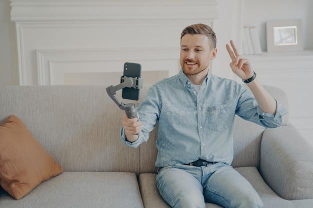 Hombre joven con barba corta con ropa casual y sentado en un cómodo sofá, video chat sosteniendo cardán con teléfono conectado, mostrando gesto de paz a la cámara