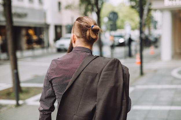 Hombre joven con barba larga en la calle de la ciudad.