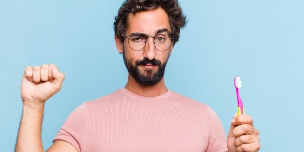 Hombre joven con barba que se siente serio, fuerte y rebelde