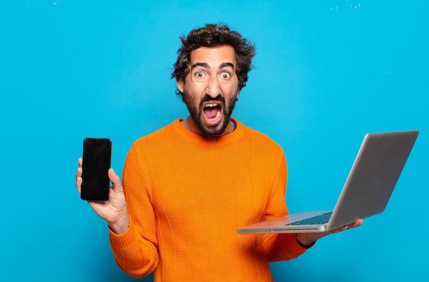Hombre joven con barba que sostiene una computadora portátil. concepto de redes sociales