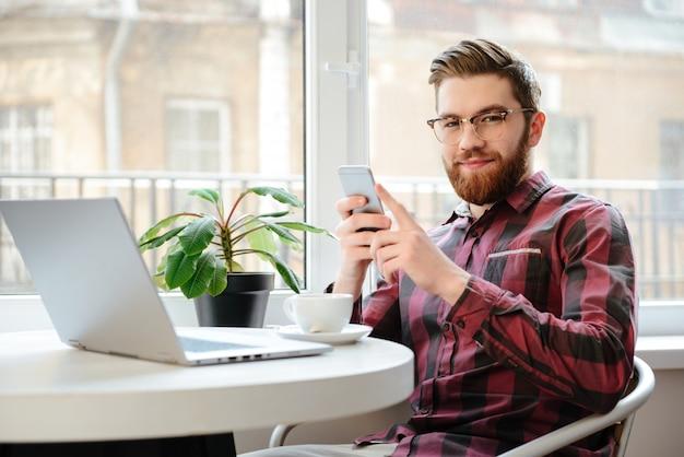 Hombre joven con barba que usa el teléfono móvil y la computadora portátil.