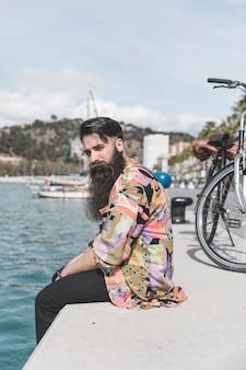 Hombre joven con barba sentado en la costa mirando a cámara