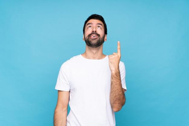Hombre joven con barba sobre azul aislado hacia arriba y sorprendido