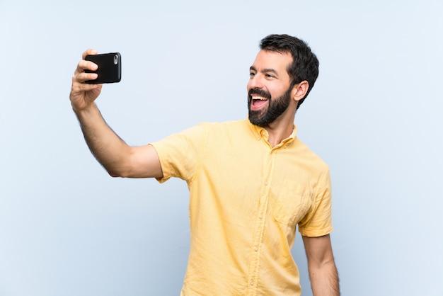 Hombre joven con barba sobre azul aislado haciendo un selfie