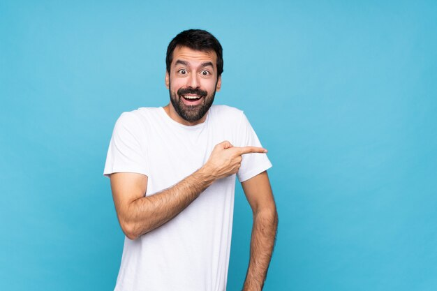 Hombre joven con barba sobre azul aislado sorprendido y apuntando con el dedo al lado