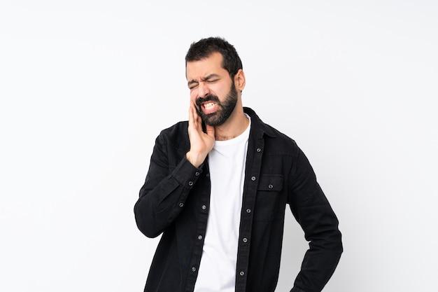 Hombre joven con barba sobre blanco aislado con dolor de muelas