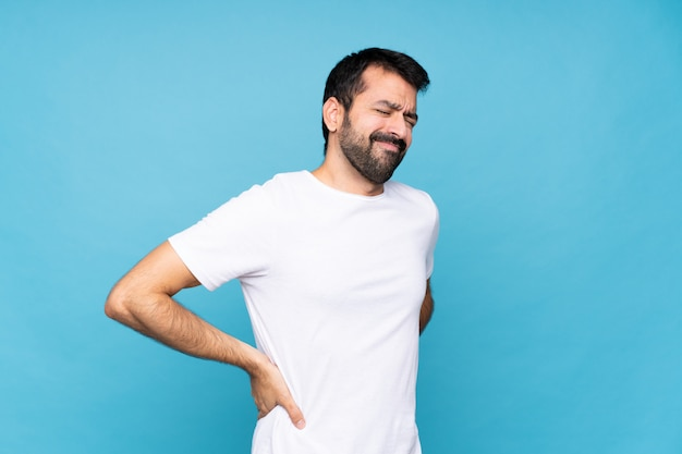 Hombre joven con barba sobre dolor de espalda aislado por haber hecho un esfuerzo