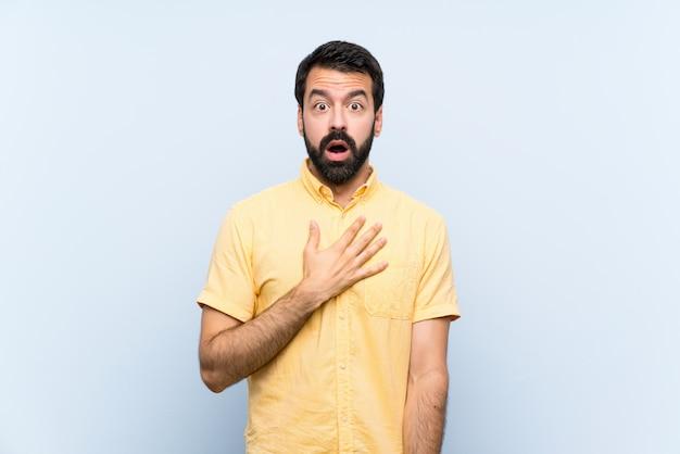 Hombre joven con barba sobre fondo azul aislado sorprendido y conmocionado mientras mira a la derecha