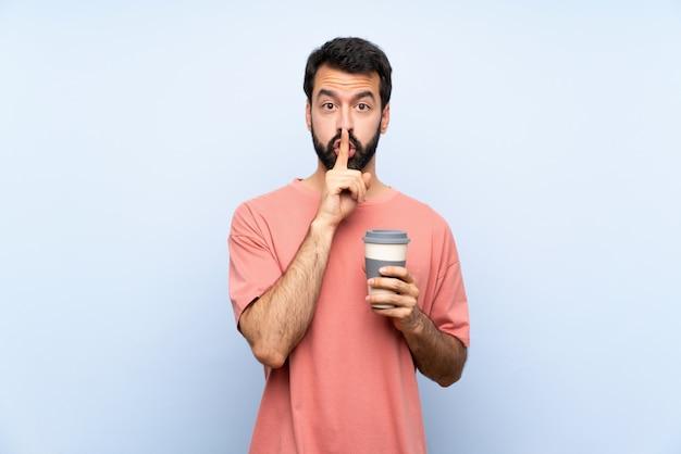 Hombre joven con barba sosteniendo un café para llevar sobre la pared azul aislada que muestra un signo de silencio gesto poniendo el dedo en la boca
