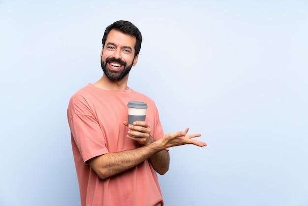 Hombre joven con barba sosteniendo un café para llevar sobre la pared azul aislada que presenta una idea mientras mira sonriente hacia