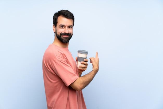 Hombre joven con barba sosteniendo un café para llevar sobre pared azul aislado apuntando hacia atrás