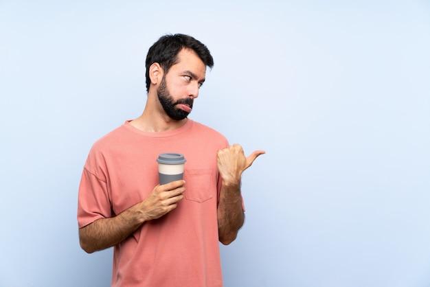 Hombre joven con barba sosteniendo un café para llevar sobre pared azul aislado infeliz y apuntando hacia el lado